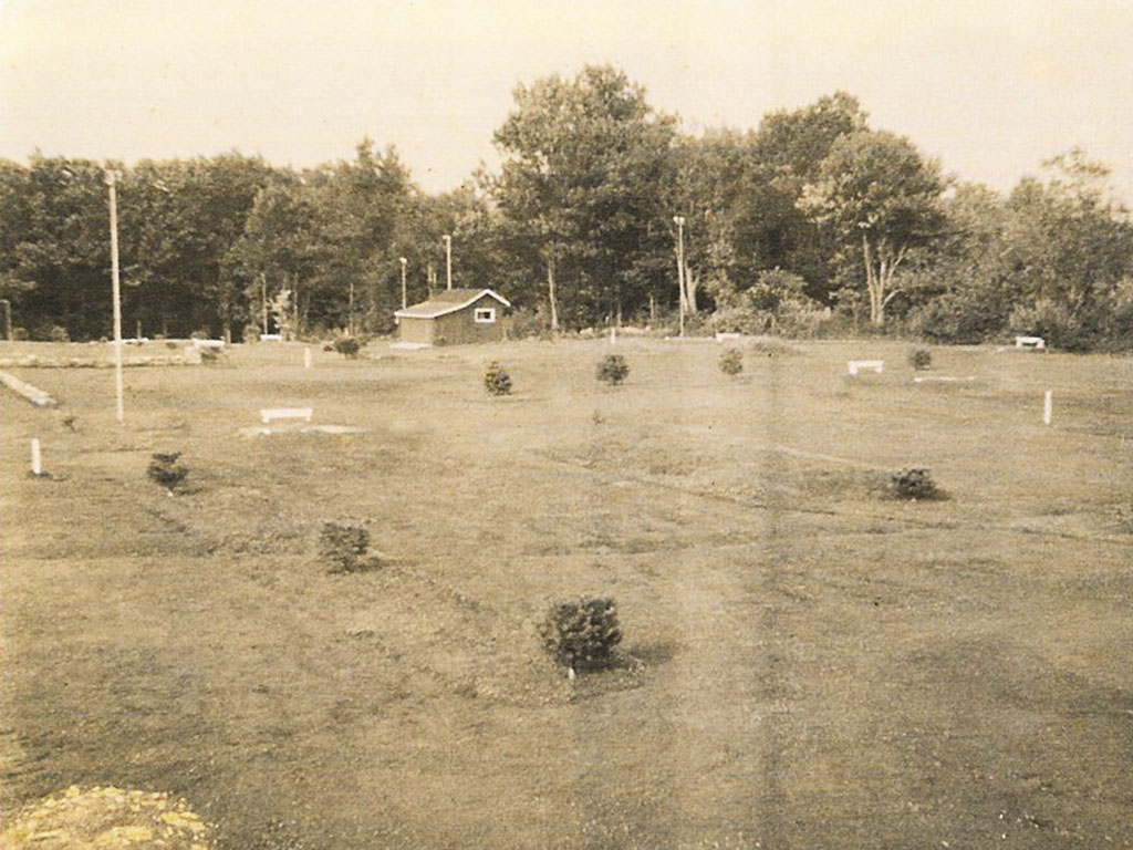 Early photo of golf course with small trees and shed in background