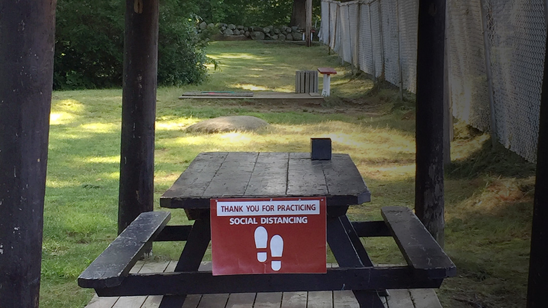social distancing sign on picnic table area